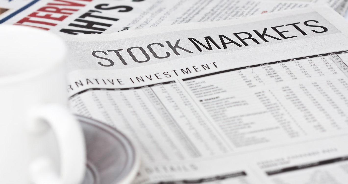 cup of coffee placed on stock market section of newspaper